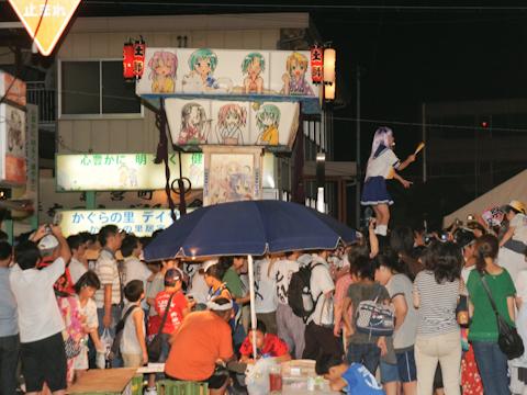 """通りの両側に並んだ露店の間を行く""""らき☆すた""""神輿。キャラの名や「萌え」を叫ぶ声が途絶えることなく続いた"""