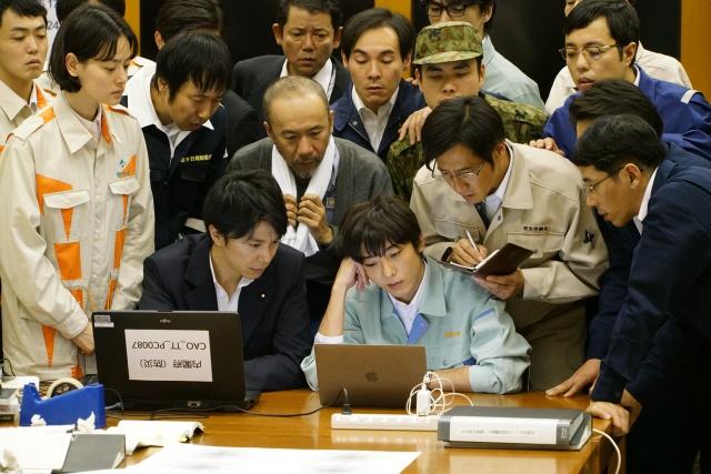 ▲生物学准教授・間邦夫役の塚本晋也さんは、中央のタオルを下げている人物。