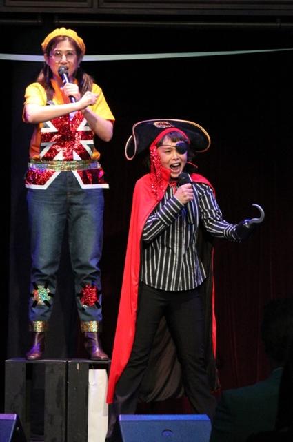 ▲スーパー歌謡ショウ「新宝島」の「宝島 ~勇気の旗を~」では雰囲気が一変。渕崎さんと高乃さんが、ジムとシルバー船長の「なんちゃって風衣装」に舞台上で生着替えを始め、さらに「新宝島」の仲間たちのイラストをステージに飾りつけていく。壮大な曲を朗々と歌いつつ、けっこうドタバタしながら作業を進める様子が最高におかしい!