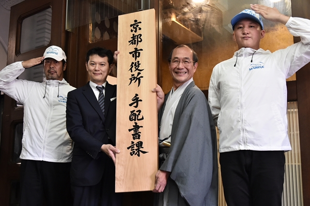 ▲京都市役所「手配書課」が設置されることになった 門川市長と中野編集長によって「手配書課」の看板が掛けられる